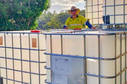 Seqwater Supply Operator Matthew Alderwick standing next to the intermediate bulk containers that are being auctioned off to provide funds to Beyond Blue